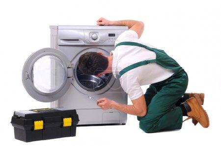 Repairman watching inside washing machine