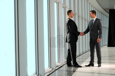 Cheerful businesspeople, or businessman and client, handshaking