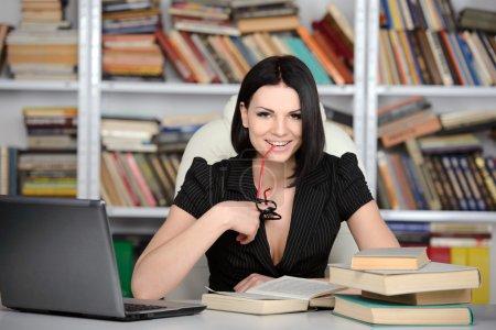 Photo pour Jeune belle femme d'affaires travaillant à la bibliothèque - image libre de droit