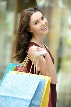 Photo pour Belle jeune femme avec des sacs de shopping dans les magasins - image libre de droit