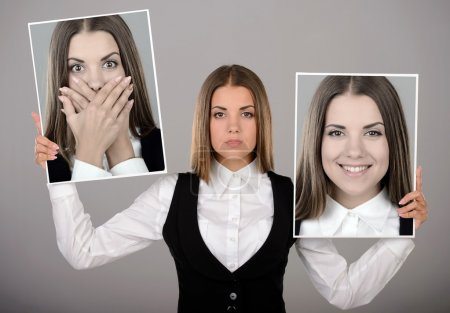 Photo for A young business woman holds two portraits of different emotions to choose from today. Gray background - Royalty Free Image