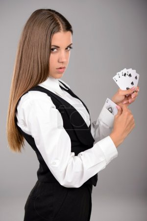 Photo for Business woman with playing cards hidden under sleeve. Gray background - Royalty Free Image