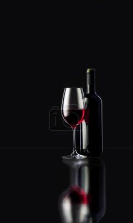 Photo pour Vin rouge en verre avec bouteille sur fond noir - image libre de droit