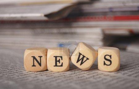 Photo pour Les nouvelles de mot sur les cubes sur un journal - image libre de droit
