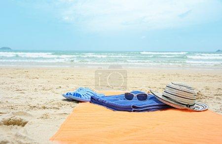 Photo pour Accessoires de plage près de la plage de sable contre la mer bleue - image libre de droit