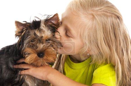 little girl kisses her dog