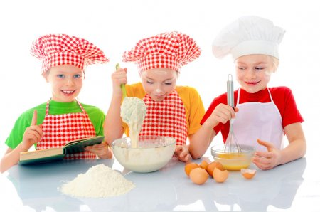 Photo for Kids with chef hats preparing tha cake dough - Royalty Free Image