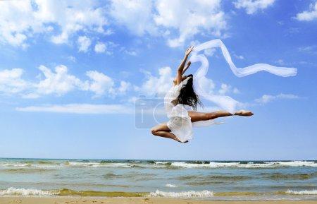 Beautiful girl jumping on the beach