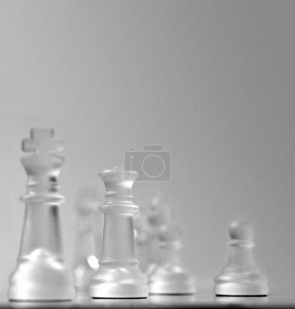 Photo pour Vue de champ peu profonde d'un échiquier centré autour de la reine blanche, d'autres pièces en mise au point douce dans un fond gris lisse. Beaucoup d'espace de copie pour la présentation et les diapositives - image libre de droit