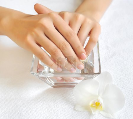 Photo pour Femme les mains dans le bol en verre avec de l'eau sur une serviette blanche - image libre de droit