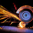 Worker cutting metal with grinder. Sparks while gr...