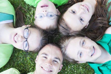 Photo pour Frères et sœurs couchés dans l'herbe verte levant les yeux - image libre de droit
