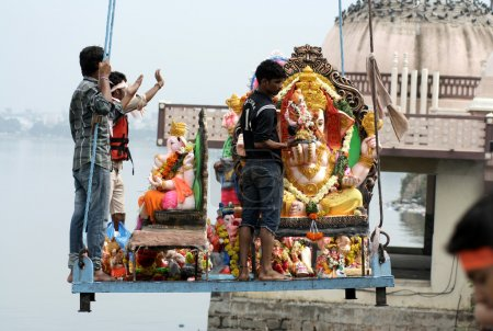 Ganesha idol lifted by crane for immersion