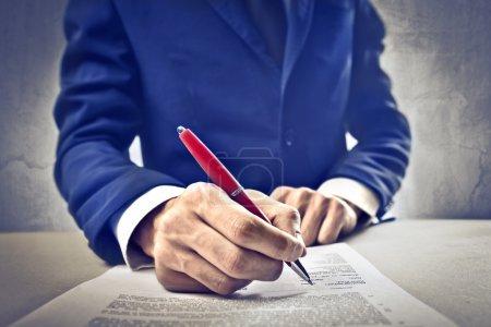 Photo pour Un homme d'affaires est signer un contrat. - image libre de droit