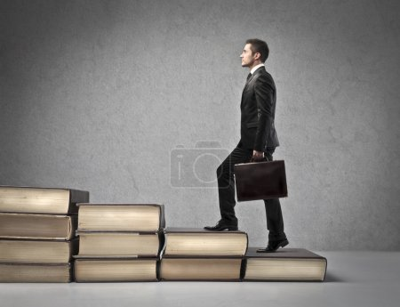 Photo for A businessman is climbing a ladder of giant books. - Royalty Free Image