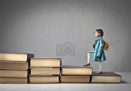 Photo for A baby is climbing a ladder of giant books. - Royalty Free Image