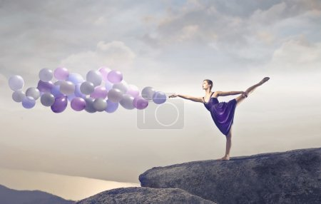 Photo for A dancer is holding some balls on a cliff. - Royalty Free Image