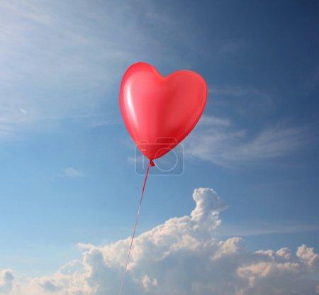Photo pour Un coeur de ballon en forme vole dans un beau ciel bleu nuageux . - image libre de droit