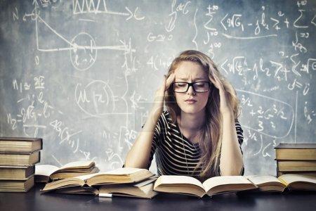 Photo pour Une belle fille blonde est stressée par l'étude . - image libre de droit