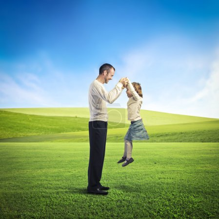 Photo for A father is playing in a large grace field with his daughter. - Royalty Free Image
