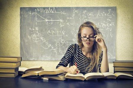 Photo pour Jeune fille blonde, étudier dans une salle de classe - image libre de droit