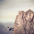 Office worker climbing the top of a rock...