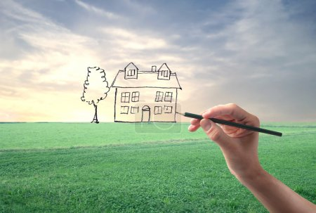 Photo for Hand drawing an house in a large grace field - Royalty Free Image