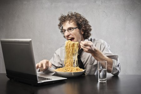 Photo for Office worker eating a plate of spaghetti while he is using a laptop computer - Royalty Free Image
