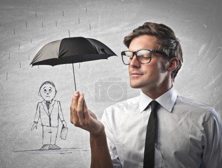 Photo pour Employé de bureau protégeant un homme dessiné avec un petit parapluie noir - image libre de droit