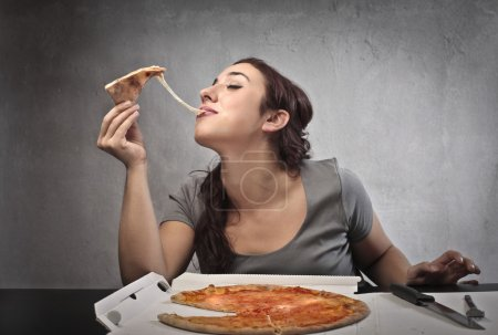Photo for Brown woman eating a pizza - Royalty Free Image