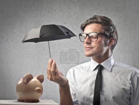 Photo pour Homme d'affaires, protéger avec un petit parapluie noir un piggy - image libre de droit