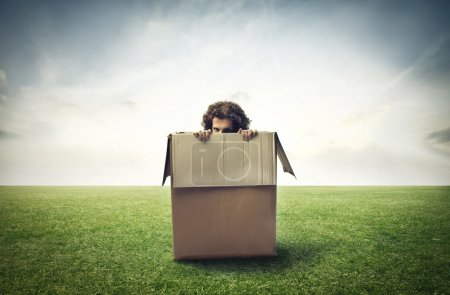 Photo for Man hiding in a box, in a large grace field - Royalty Free Image