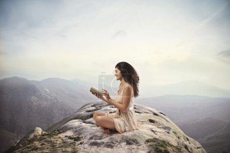 Photo pour Fille brune lisant un livre au sommet d'une montagne - image libre de droit