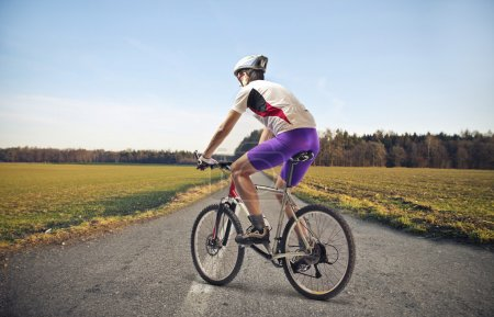 Photo for Cyclist on a long road of countryside - Royalty Free Image