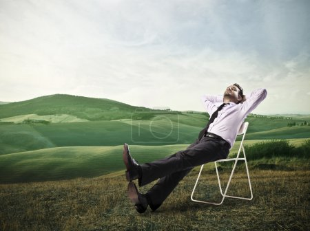 Photo for Businessman lying on a chair in a large field - Royalty Free Image