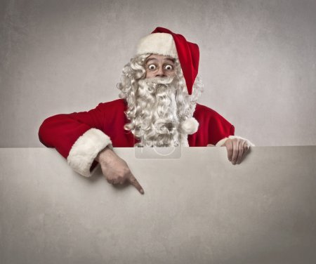 Photo for Santa Claus showing something on a white big cardboard - Royalty Free Image