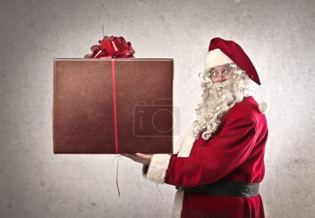 Photo for Santa Claus holding a large package containing a gift - Royalty Free Image