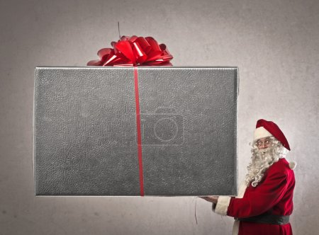 Photo for Santa Claus holding a very big present - Royalty Free Image