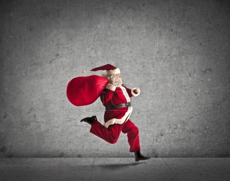 Photo for Santa Claus running with his bag full of presents - Royalty Free Image