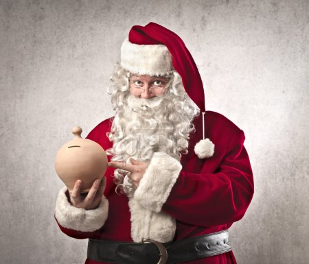 Photo for Santa Claus holding a vessel for the money - Royalty Free Image