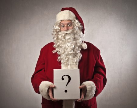 Photo for Santa Claus holding a small cardboard on which is drawn a question mark - Royalty Free Image