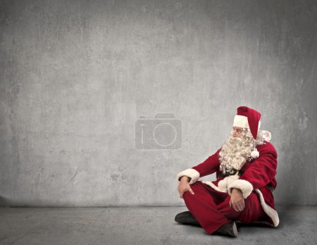 Photo for Santa Claus sitting near an empty dark white wall - Royalty Free Image
