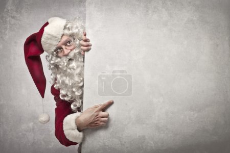 Photo for Santa Claus indicating something on a white wall - Royalty Free Image