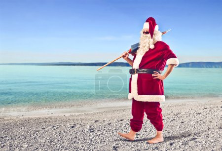 Photo for Santa Claus holding a beach umbrella on a beach - Royalty Free Image