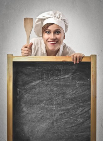 Photo for Woman cook holding an empty blackboard - Royalty Free Image