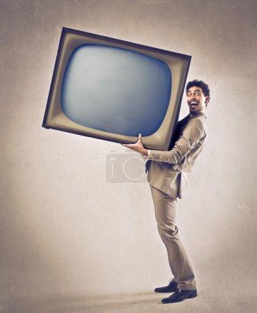 Photo pour Jeune homme tenant une grande télévision - image libre de droit