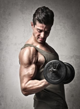 Photo for Man raising a dumbbell with his right arm - Royalty Free Image