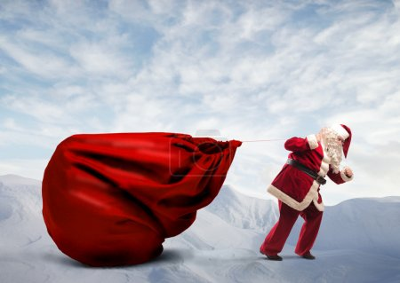 Photo for Santa Claus dragging a big red sack on a white mountain - Royalty Free Image