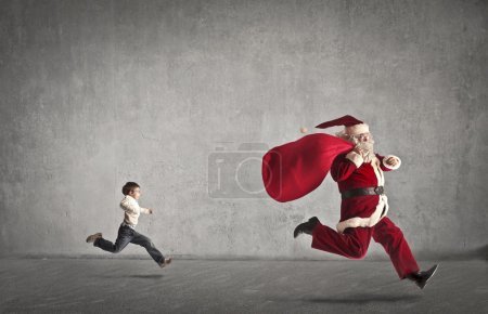 Photo for Santa Claus running away from a child - Royalty Free Image