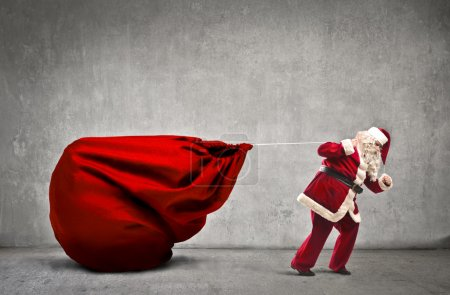Photo for Santa Claus dragging a big red sack - Royalty Free Image